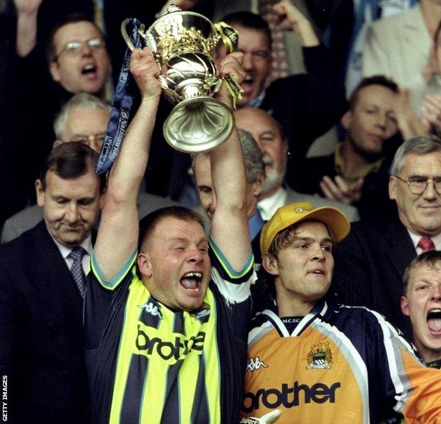 Andy Morrison lifts the trophy as Man City win the League One play-off final