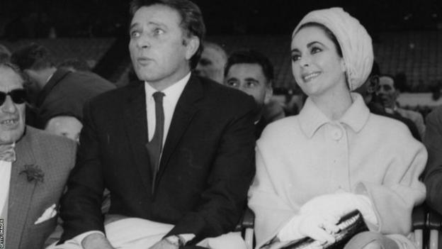 Richard Burton and Elizabeth Taylor have front row seats for Ali's fight with Henry Cooper at Wembley Stadium in 1963