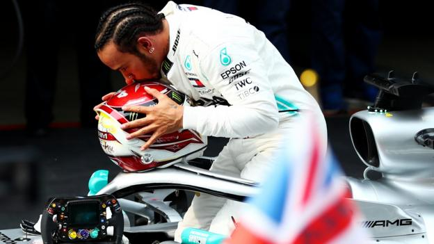 Lewis Hamilton celebrates on his car as he wins the Chinese GP and the 1,000th race in the Formula 1