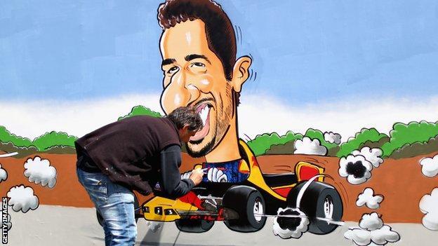 An artist paints a Daniel Ricciardo mural