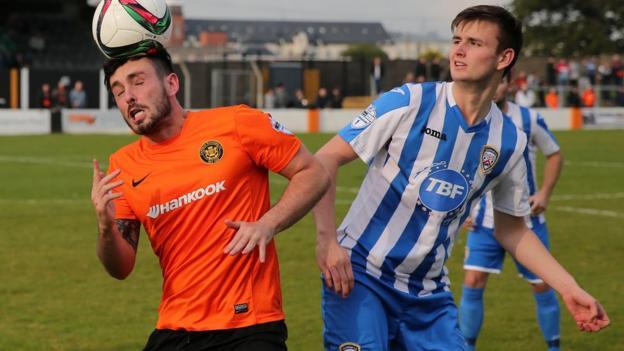 Brian McCaul of Carrick Rangers heads the ball clear as Coleraine opponent Adam Mullan closes in