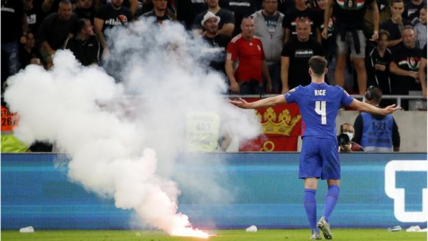 Hungary fans throw a flare on the pitch in front of England players