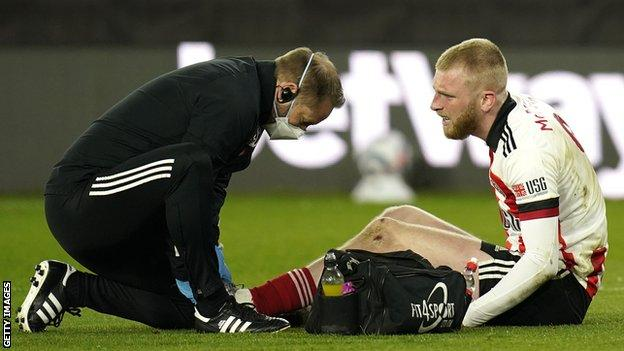 Sheffield United striker Oli McBurnie (right) receives treatment from a physio (left) for a foot injury during a Premier League game against Arsenal