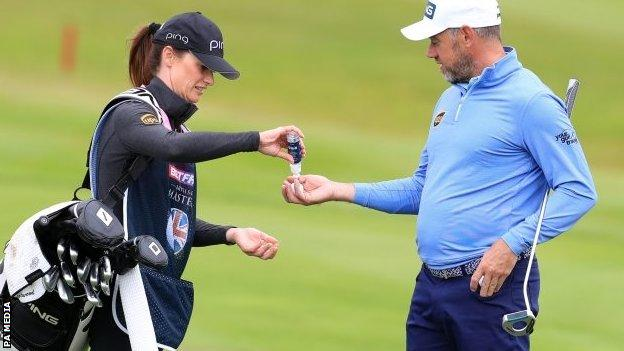 Lee Westwood gets hand sanitiser from caddie and girlfriend Helen Storey