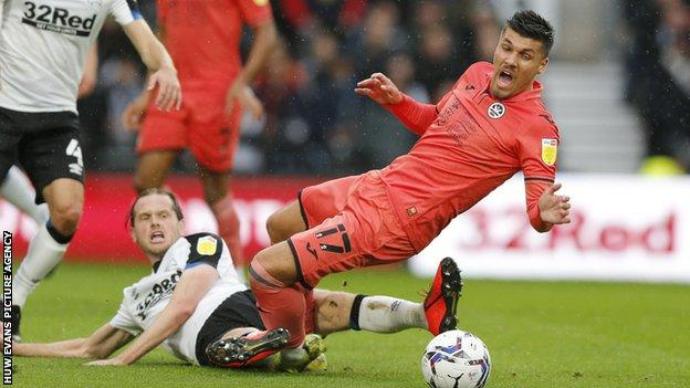 Richard Steadman, who was forced off injured before the break, challenges Swansea's Joel Piroe