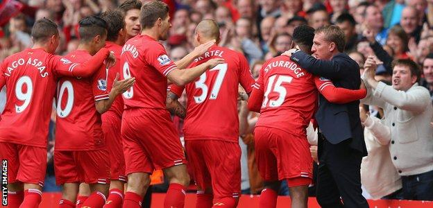 Brendan Rodgers hugs Daniel Sturridge as other Liverpool players celebrate after Sturridge scored the opening goal against Manchester United at Anfield in 2013