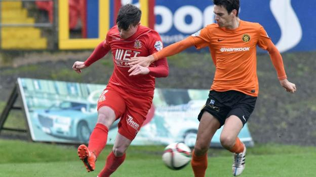 Portadown midfielder Peter McMahon gets his pass away despite close attention from Carrick Rangers opponent Mark Surgenor