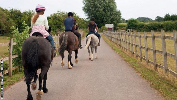 Three ponies being ridden into the distance