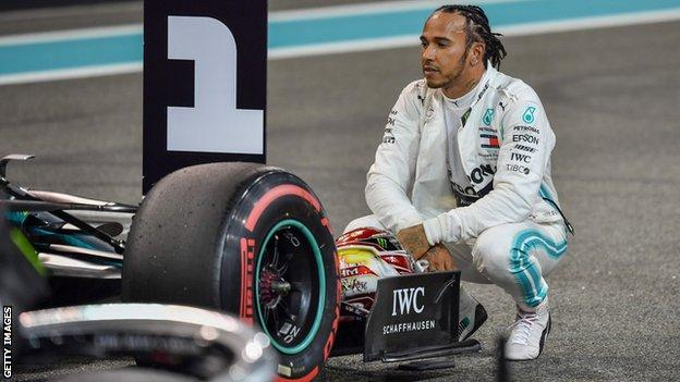 Lewis Hamilton kneels be his car after taking pole in Abu Dhabi