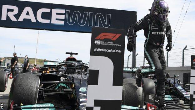 Lewis Hamilton jumps off his Mercedes after winning the race