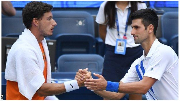 Novak Djokovic shakes hands with Pablo Carreno Busta after US Open default
