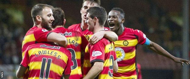 Partick Thistle players celebrate Andrew Davies' own goal