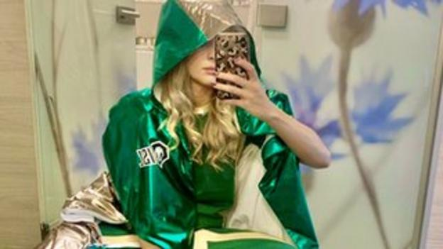 Siobhan-Marie O'Connor takes a selfie wearing a green embroidered cape