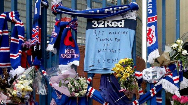 Scarves and flowers left on the gates outside Rangers' Ibox stadium where Ray Wilkins spent three seasons as a player