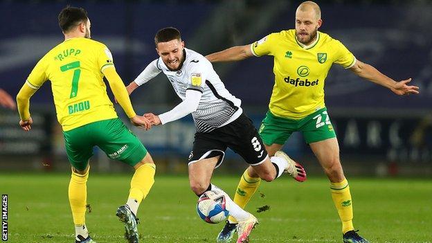 Norwich striker Teemu Pukki tangles with Swansea captain Matt Grimes