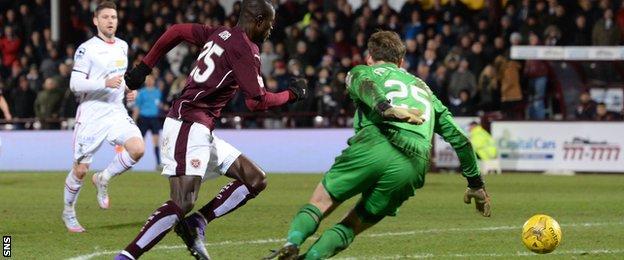 Hearts' Abiola Dauda rounds goalkeeper Owain Fon Williams