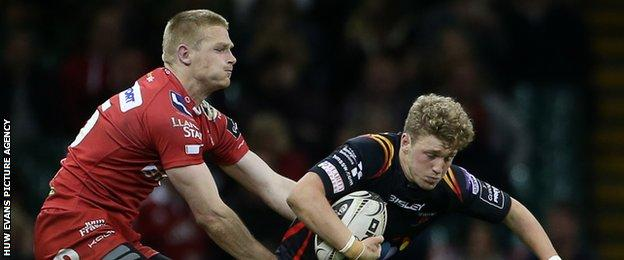 Angus O'Brien of Newport Gwent Dragons is tackled by Johnny Mcnicholl