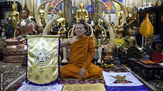 Thai Buddhist monk Phra Prommangkalachan holding a banner emblazoned with sacred patterns surrounding Leicester City Football Club's crest as he poses for pictures at the Traimitr Withayaram Woraviharn Temple in Bangkok