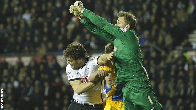 Preston keeper Anders Lindegaard punches clear