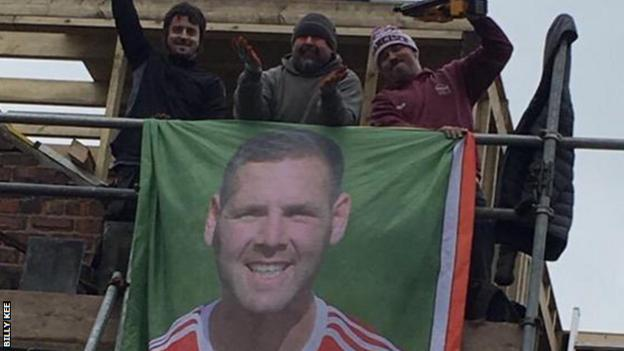 Workers on a building site near Leicester unfurl a banner of former Accrington Stanley striker Billy Kee