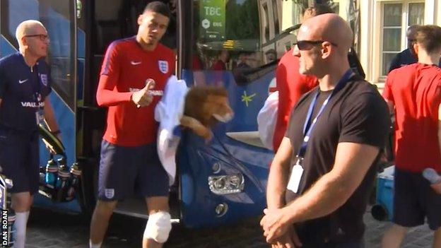 Chris Smalling leaves the England team bus after training on Tuesday - with his knee strapped and iced