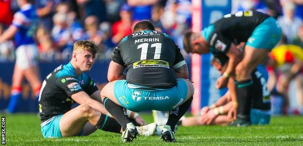 Leeds Rhinos players slumped on the turf after another loss