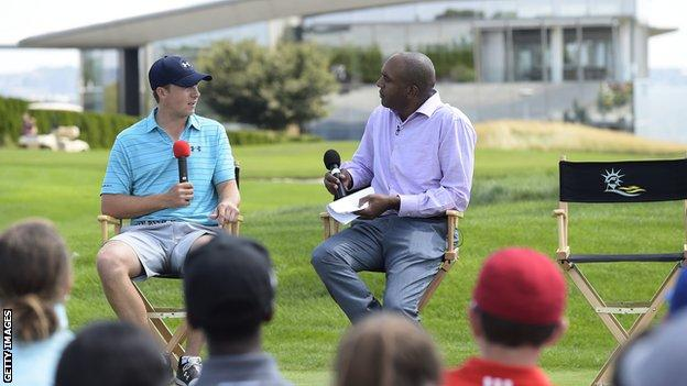 Jordan Spieth and Damon Hack sit in chairs on a golf course and talk into microphones