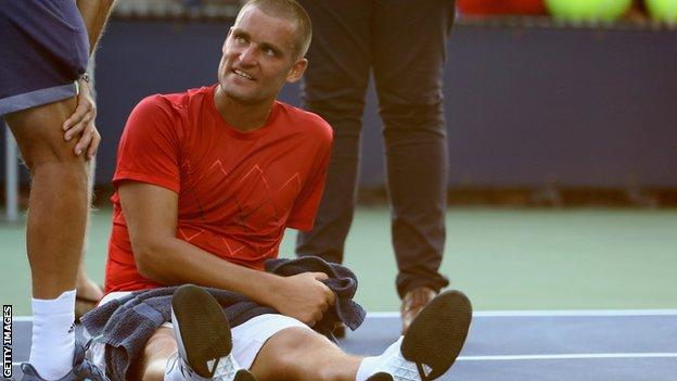 Mikhail Youzhny is treated on court before retiring in his US Open first-round match