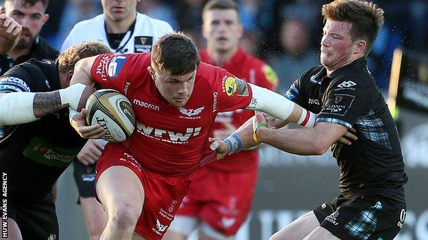 Steff Evans tries to break free from Siua Halanukonuka and George Horne at Glasgow