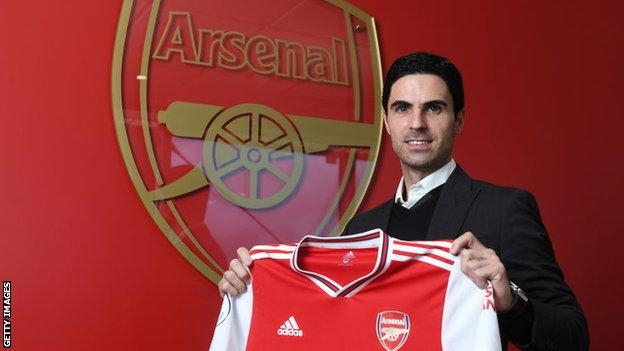 Mikel Arteta holding an Arsenal shirt after being appointed head coach