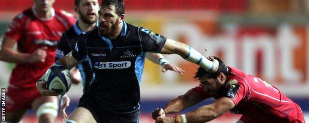 Glasgow's Sean Lamont holds off a challenge against Scarlets