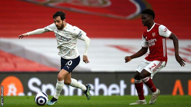 Bernardo Silva of Manchester City gets past Bukayo Saka of Arsenal on Sunday