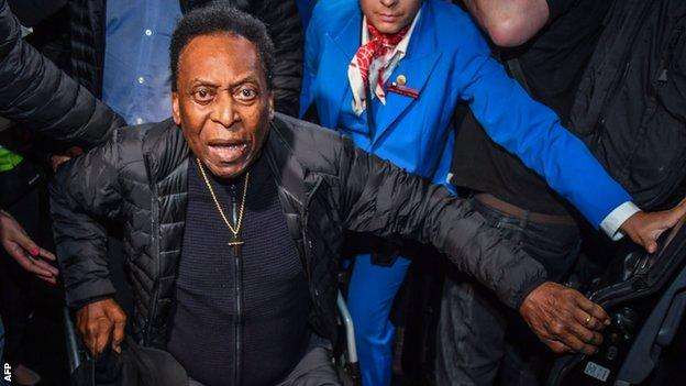 Pele being helped out of a wheelchair in 2019