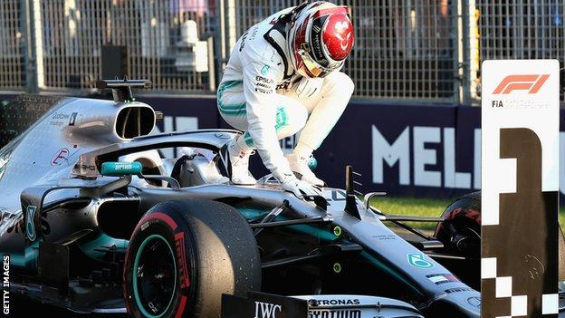 Lewis Hamilton celebrates on his car after claiming pole position in Melbourne