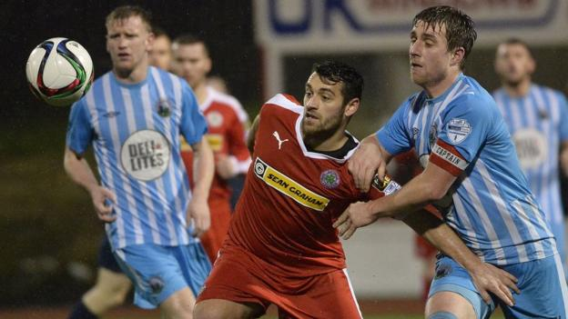 Cliftonville striker David McDaid tries to hold off Warrenpoint Town opponent John Boyle at Solitude