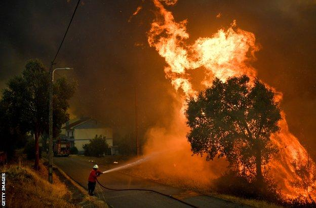 Ένας πυροσβέστης αντιμετωπίζει μια δασική πυρκαγιά κοντά στο χωριό Bocarica στο Abrantes στις 10 Αυγούστου 2017.