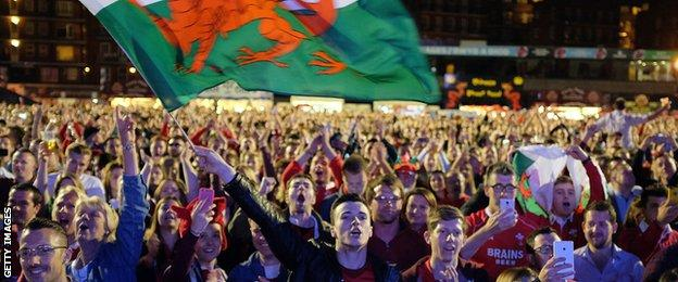 Supporters waving Wales flags celebrate in one of the World Cup fan zones