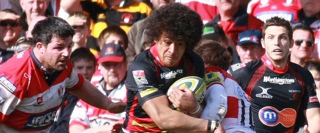 Dragons Taulupe Faletau being tackled by Gloucester's Nicky Robinson