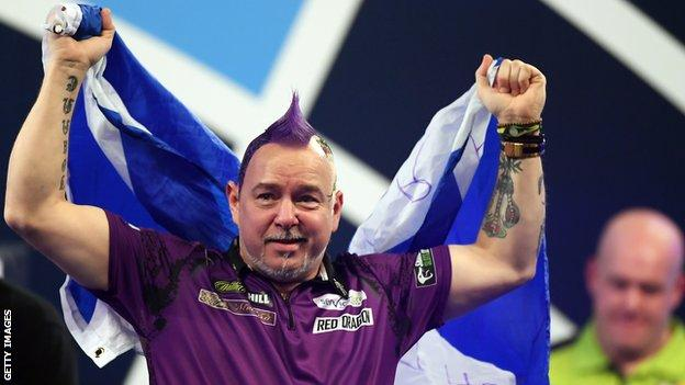 Peter Wright (left) holds up the Scotland flag as he celebrates beating Michael van Gerwen (right) to win the 2020 PDC World Darts Championship