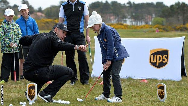 Lee Westwood teaches a young girl golf