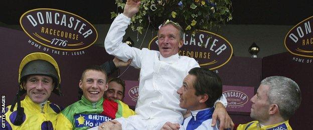 Pat Eddery is hoisted aloft by his fellow jockeys after his final race in 2003