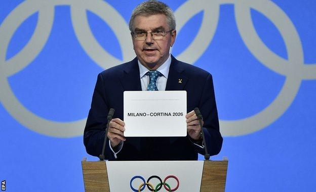 IOC president Thomas Bach opens the envelope announcing Milan-Cortina has won the bid