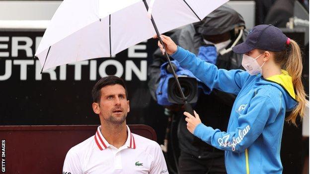 Novak Djokovic sits under an umbrella