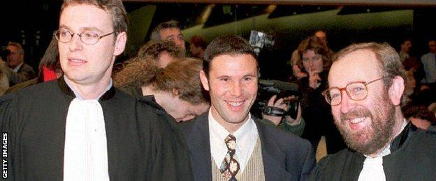 Belgian soccer player Jean-Marc Bosman, flanked by two of his lawyers Luc Misson (R) and Jean-Louis Dupont (L), smiles as the European Court of Justice rules 15 December 1995 that the transfer system of players between football clubs was illegal.