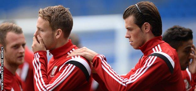 Chris Gunter gets a helping hand from Wales team-mate Gareth Bale in training