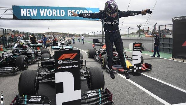Lewis Hamilton jumps off his car after winning the Portuguese Grand Prix