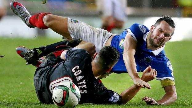 Opposing skippers Colin Coates of Crusaders and Linfield's Andrew Waterworth hit the deck during the Irish Premiership clash at Windsor Park