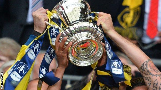 FA Cup trophy held aloft by Arsenal players