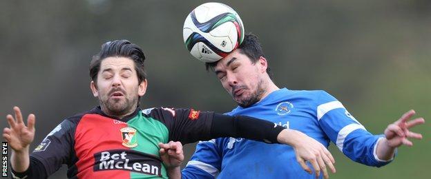 Glentoran's Curtis Allen fights out an aerial duel with Ballinamallard's Emmet Friars
