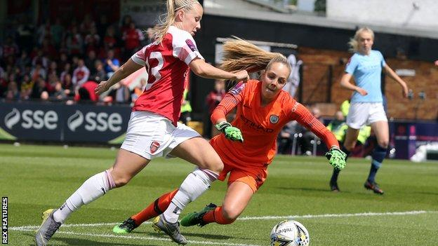 Manchester City goalkeeper Ellie Roebuck attempts to smother an effort from Arsenal striker Beth Mead